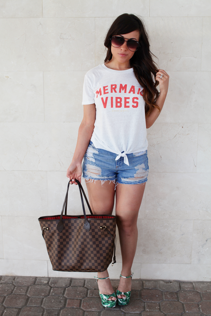 See how fashion, lifestyle, and beauty blogger Little Tree Vintage styles ripped denim shorts, palm tree espadrilles, and a graphic tee for Summer.